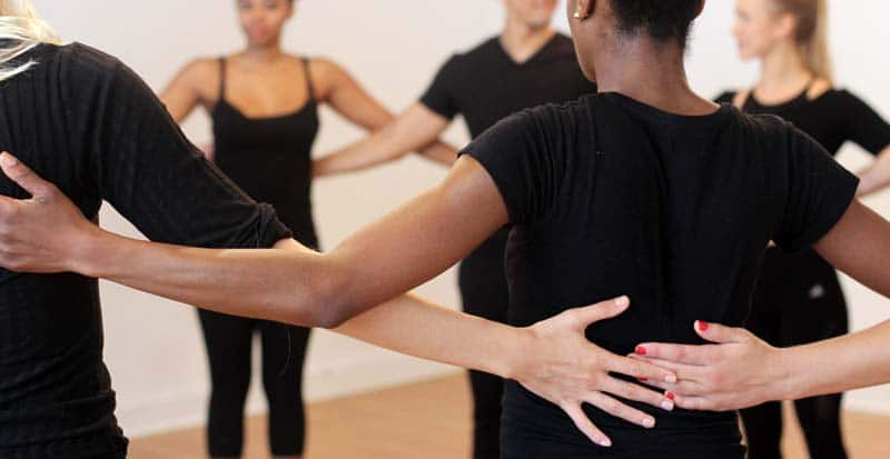 students in movement class with Briana form a circle during a movement exercise
