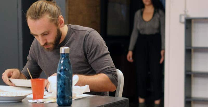 a student is at the table in the acting conservatory new york ny at maggie flanigan studio waiting for the student who is at the door