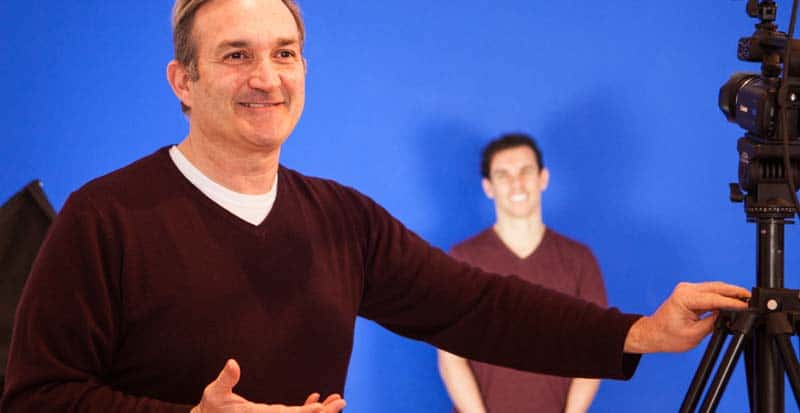 instructor in commercial acting class at an acting school Chinatown NY - here he stands in front of a blue screen session with student