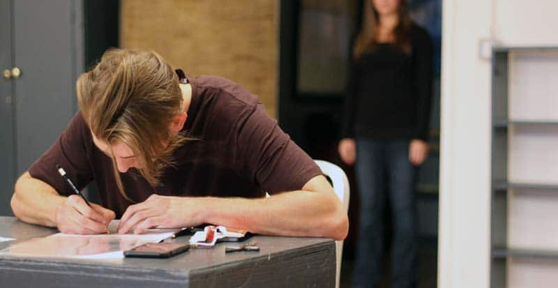 a student in the core acting program sits at a table writing during a Meisner exercise at Maggie Flanigan Studio