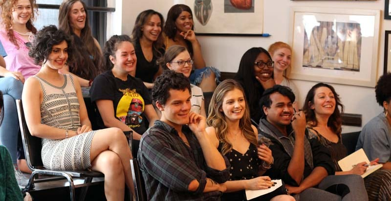 students at Maggie Flanigan Studio smiling listening to Charlie Sandlan in the Professional Actor Training Program (PATP)