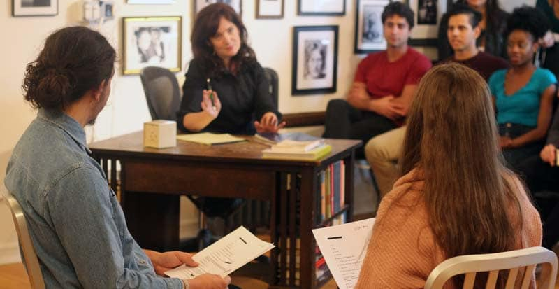 This is an image form the summer acting program and the meisner intensive at the maggie flanigan studio. Karen chamberlain is talking to students while they are reading a script